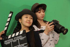 2 девочки, фотоаппарат, кино-хлопушка, зелёный фон